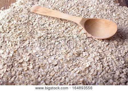 Oat flakes texture with wooden spoon. Oat for breakfast