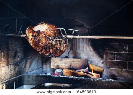 Pork ham on open flame. Slab of pork ham on a spit grilling