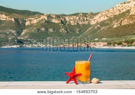 Glass of fresh orange juice next to shells on the seaside landscape background. Fresh orange juice, seaside and seashells. Horizontal. Daylight.