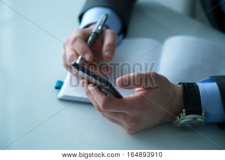 Man working in the office and holding keeps his phone