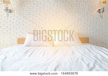 white Pillow on white bed with brickwall background