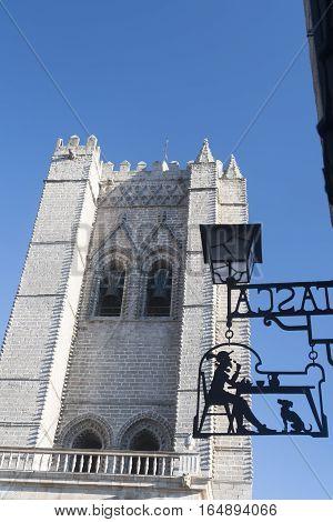 AVILA, SPAIN - JULY 23, 2016: Avila (Castilla y Leon Spain): historic cathedral belfry and a shop sign