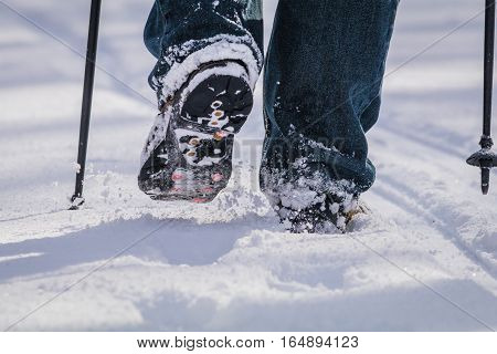 Closeup of person walking in fresh snow with snow poles