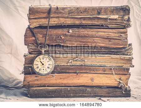Pile of old dusty books with broken pocket watch on dirty white cloth.