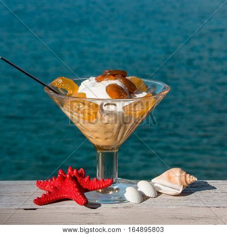 The bowl of greek yogurt with caramelized grapes for breakfast near seashells, red starfish on the sea background. Greek yogurt with caramelized grapes by the sea and seashells. Daylight.