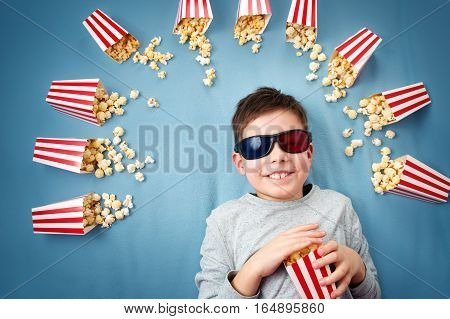 Child lying on blue background in 3d glasses and watching tv. Boy eating popcorn