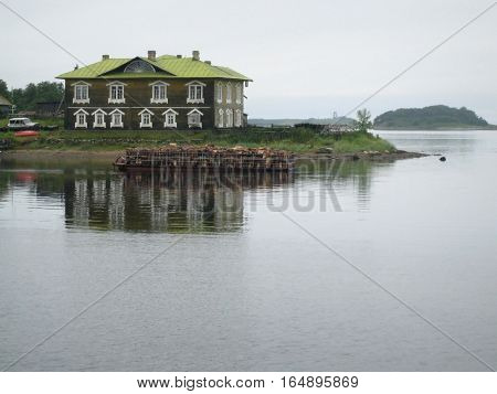 Old wooden house and barge with wood at Solovki Island Russia