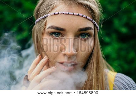 technologies beauty and lifestyle concept -Happy vaping young white blonde girl. smoking fruit flavored e-liquid or e-juice with vaporizer device or e-cig.Modern gadget for smokers
