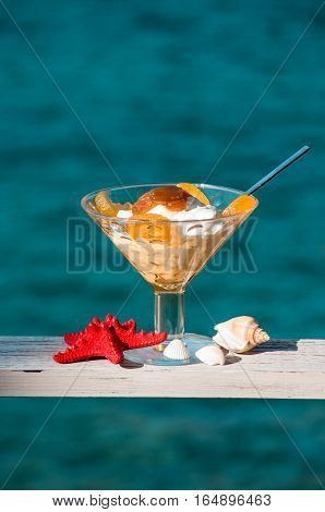 The bowl of greek yogurt with caramelized grapes for breakfast near seashells, red starfish on the sea background. Greek yogurt with caramelized grapes by the sea and seashells. Vertical. Daylight.