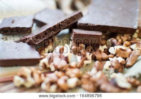 Chocolate and nuts lying on a wooden table.