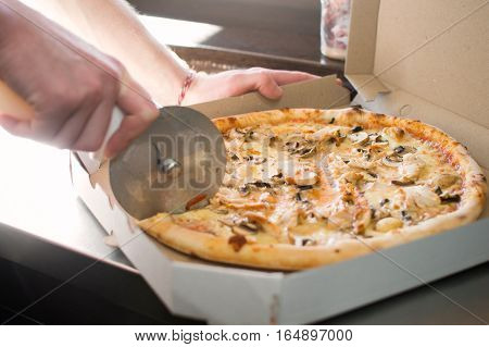 Cutting to cook pizza with olives in the box by the window.