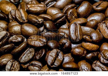 Closeup of coffee beans whole roasted in dark brown golden color