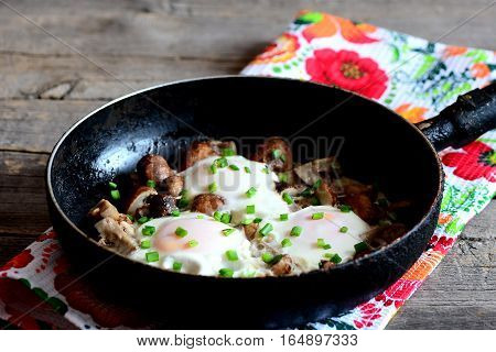 Delicious fried eggs with chopped mushrooms and fresh green onions in pan. Vegetarian egg recipe. Breakfast or lunch idea. Old wooden background. Rustic style. Closeup