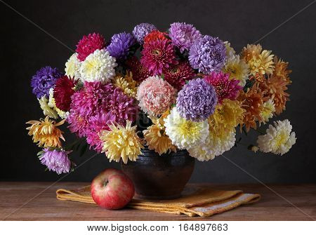 Still life with a bouquet of chrysanthemums in a jug and red Apple.