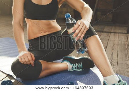 Young athletic woman is drinking water after training on the sport mat