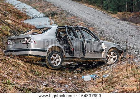 Silver colored stolen car that have been crashed and ditched on the side of a dirt road. Totally vandalized and wrecked.