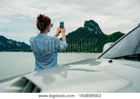 woman traveler taking pictures on the smartphone landscape mountain. Stop in the journey for taking photos and share them on social networks.
