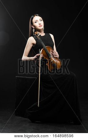 Girl in black dress standing on black background with a wooden violin