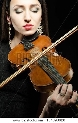 Portrait of a young woman who plays the violin with closed eyes on a black background