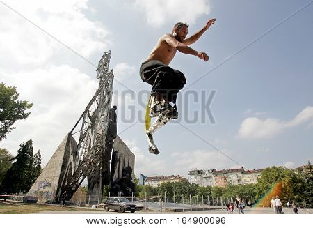 SOFIA BULGARIA - SEPTEMBER 18: A young man jumps with jumping stilts in front of monument
