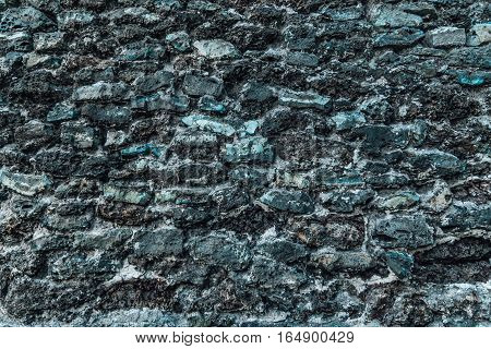 Old corroded wall made from blue slag (Cinder) stones