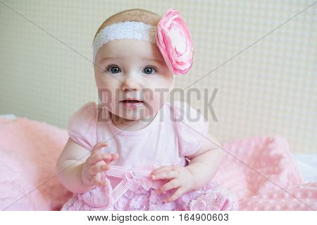 little girl in a pink dress sits on the bed.