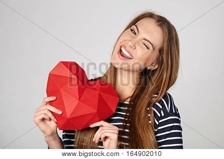 Playful emotional woman showing red polygonal paper heart shape winking at camera