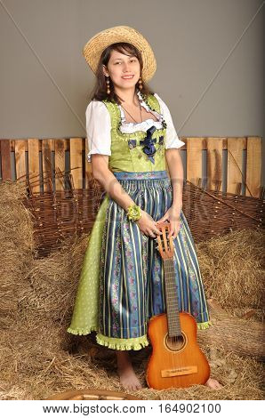 The girl in a dress with a guitar in the hayloft