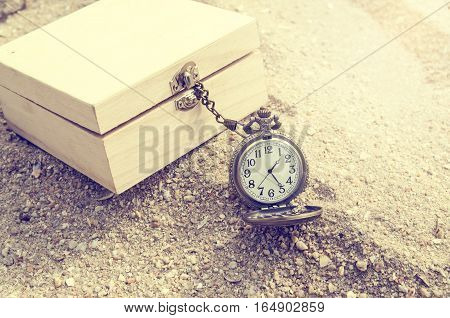 Antique pocket clock in a treasure chest on a beach