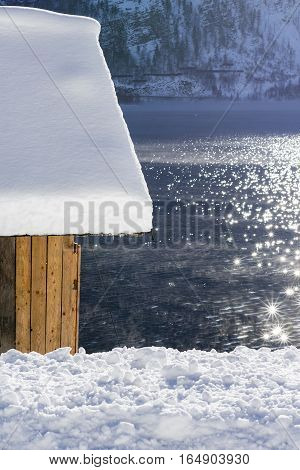 Old Wooden Snow Covered Boathouse At Mountain Lake. Winter Landscape.