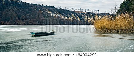 Old fishing boat on a frozen lake, Rusenski Lom park, Ruse district, Bulgaria.