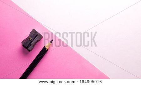 Pencil and sharpener on pink paper with a white background