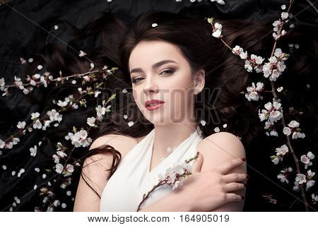Spring beauty consept. Portrait of a fashionable model with curly brown hair sexy red lips lying on black background with spring trees blossoming branches and petals background. Studio portrait shot of gorgeous woman in white dress with perfect make-up se