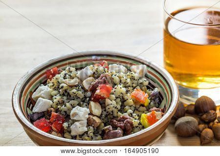 Christmas kutia and uzvar. Traditional ukrainian cereal wheat porridge with raisins, nuts, poppy seeds, honey and candied fruit in earthenware bowl with dried fruit drink on natural wood table