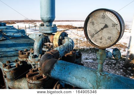 Bucharest Romania December 30 2012: Slate gas or oil equipment with many pipelines valves connectors panel and motors are seen on a field outskirts Bucharest.