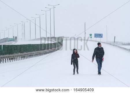 Highway 2 Romania December 29 2014: A couple is walking on the highway A2 the main commercial route which connects Bucharest to the Black Sea's port Constanta closed during a blizzard.