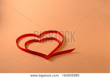 A Single Red Heart Of Ribbon On A Light Warm Beige Background