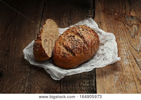 Bread with butter-paper on wooden background. Close-up