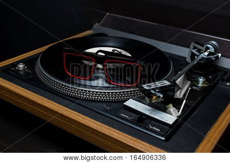 Vintage 1970s record player with a sunglasses over the acetate disc, Dj accessories