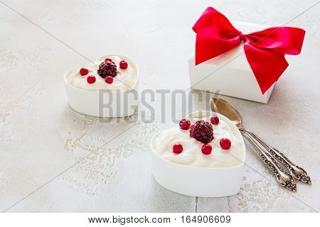 Valentine day decoration breakfast yogurt with berries for two in white heart-shaped bowls and gift box on the table.