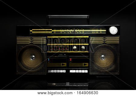 Vintage boom box on black background. Radio cassette