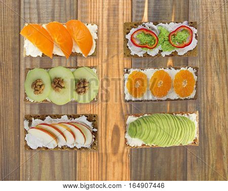 Sandwiches with cream cheese and fresh berries fruits and vegetables. Fresh healthy appetizer snack with crispbread on a wooden background.
