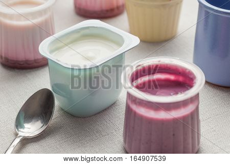 Yogurts Assortment  In Plastic Bowls On White Textile Background. Natural And Fruit Healthy, Diet, G