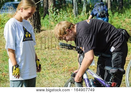 Vinzili, Russia - September 4, 2005: Velodanger competition in territory of unfinished psychiatric hospital. Young man checking bicycle of girl. Tyumen region