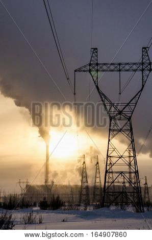 Gas power station in cold winter landscape during sunset. Pipes with smoke. Power transmission tower foreground. Energy industry concept. Toned.