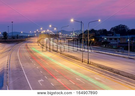 Car light trails on motorway with beautiful skyscape at twilight time