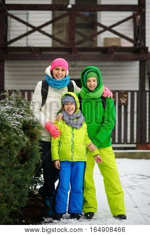 Mother with two sons on walk in winter day. All are dressed in bright ski suits. The family stands having embraced. Against the background of the beautiful bushes which are strewn lightly with snow.
