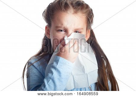 Little girl is blowing her nose isolated on white