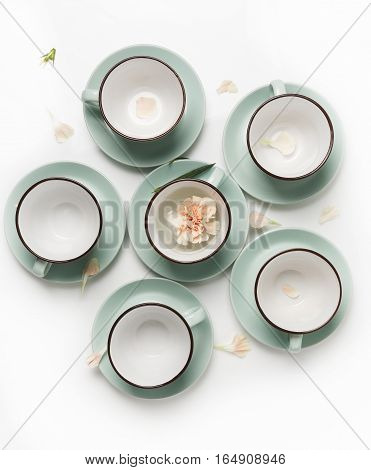 Clean dishes, coffee or tea set. Plenty of elegant porcelain cups and saucers with flower inside at white background, high key, top view and flat lay.