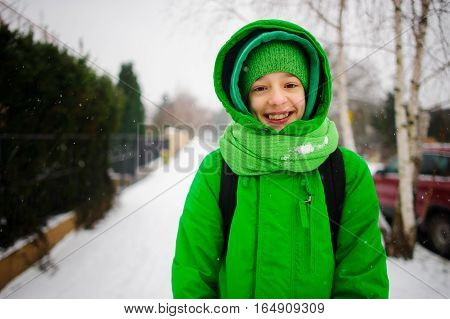 The cheerful teenager goes down the street in winter day. Behind shoulders at him a backpack. The boy is dressed in a bright green ski suit. It is snowing. The fellow smiles from pleasure.